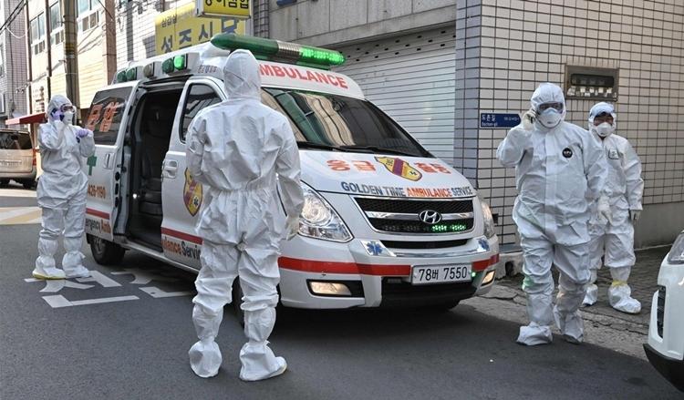 Nhân viên y tế Hàn Quốc mặc đồ bảo hộ đến thăm nơi cư trú của những người nghi nhiễm nCoV để lấy mẫu xét nghiệm. Ảnh: AFP