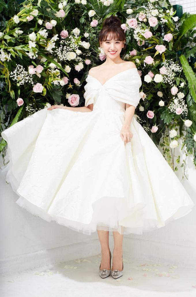 <p> Hari Won chọn không gian đầy hoa tươi nhằm mang đến hình ảnh ngọt ngào. Chiếc váy trắng đơn giản, điểm nhấn xẻ ngực sâu giúp Hari Won khoe vẻ gợi cảm. Phom dáng phồng kiểu công chúa nữ tính.</p>