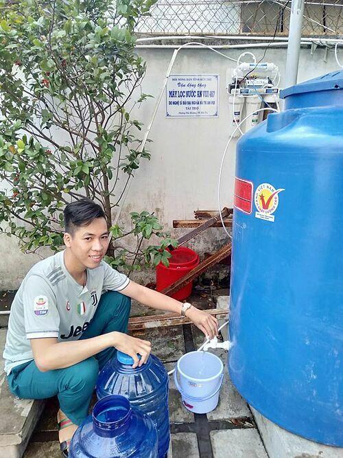 Người dân dùng máy lọc nước Đại Nghĩa tặng.