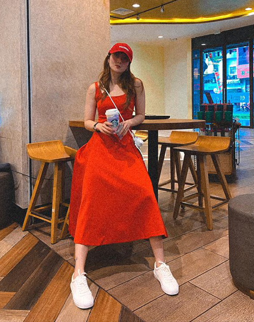 Bộ đầm đỏ tưởng như chỉ để diện đi tiệc được Yến Nhi biến thành đồ street style cực chất bằng cách mix với sneakers và mũ lưỡi trai.