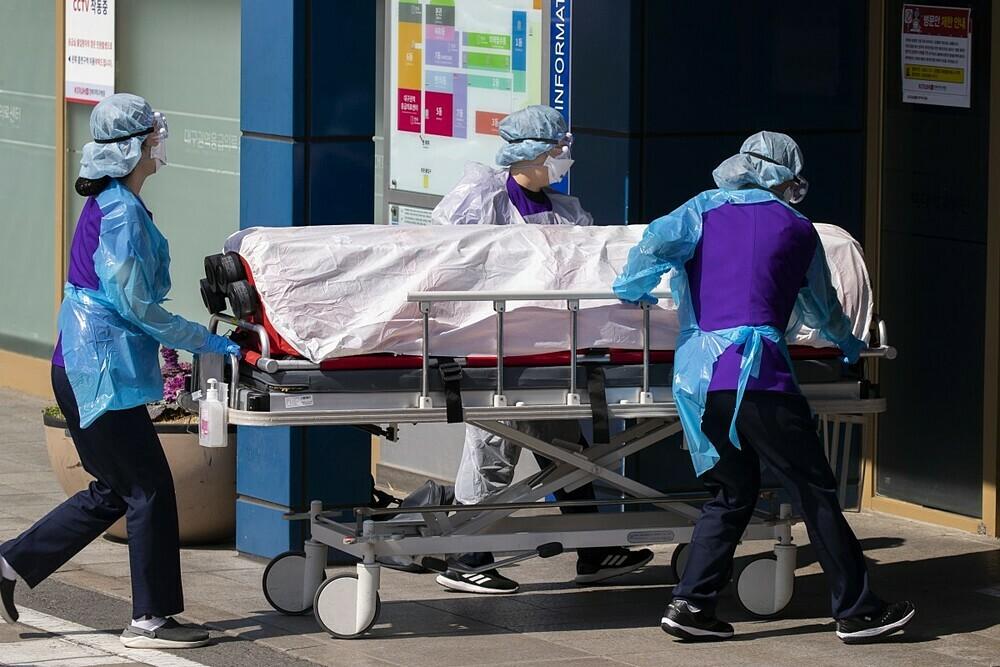 Nhân viên y tế chuyển bệnh nhân nhiễm nCoV ở Deagu. Ảnh: Xinhua.