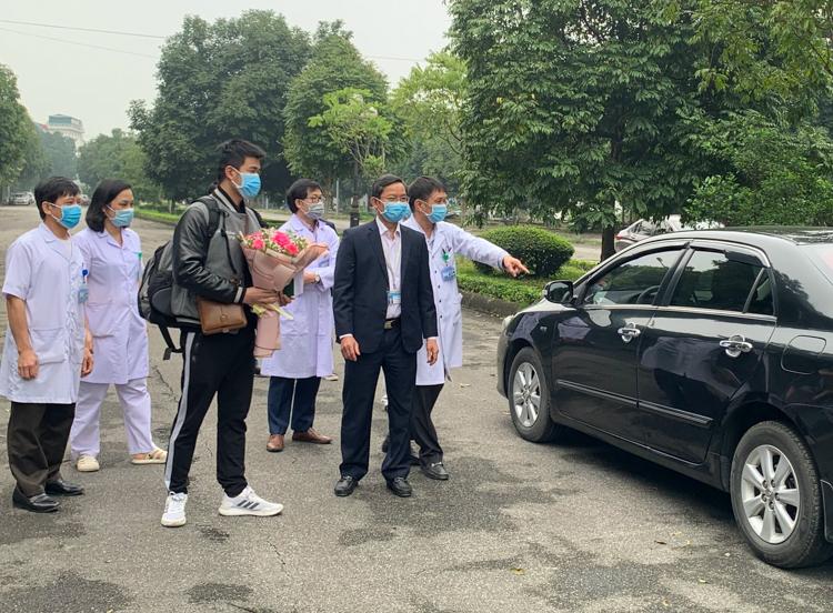 Bệnh nhân 18 (ôm hoa) sáng 20/3 được xe của bệnh viện Ninh Bình đưa về nhà ở huyện Vũ Thư, tỉnh Thái Bình, và cách ly giám sát y tế tại nhà. Ảnh: Mỹ Hạnh.