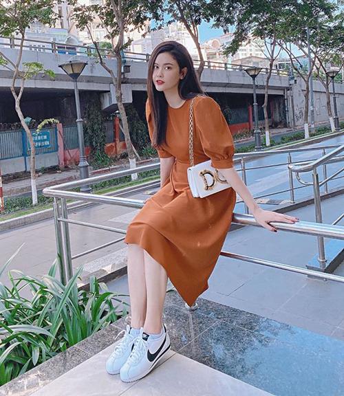 Trương Quỳnh Anh trẻ trung trên phố với váy cam, giày Nike và túi Dolce & Gabbana.