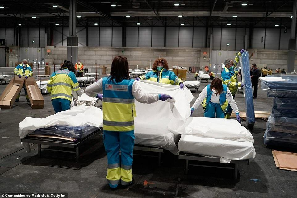 Nhân viên y tế sắp xếp giường trong bệnh viện dã chiến ở Madrid để chuẩn bị đón bệnh nhân.