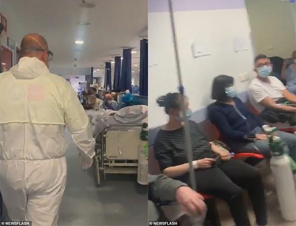 Một nhân viên y tế đi qua dãy hành lang ở bệnh viện Severo Ochoa de Leganes, bệnh nhân nằm trên cáng dọc hai bên với nhiều người khác đang chờ đợi.