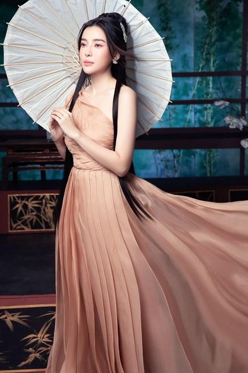 Cao Thái Hà sử dụng ô làm đạo cụ chụp hình. Thiết kế kiểu dáng lệch vai, chất liệu lụa giúp cô khoe xương quai xanh.