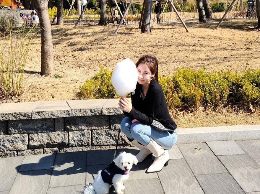 Seo Hyun dắt cún cưng đi dạo công viên. Cô nàng như trở về tuổi thơ với cây kẹo bông gòn.