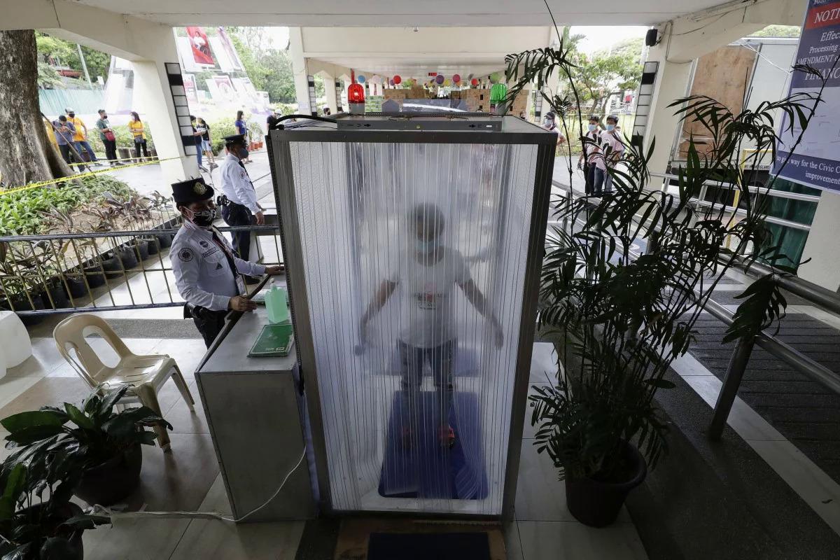 Người dân được khử trùng trong buồng trước khi vào tòa thị chính địa phương ở Manila, Philippines. Ảnh: AP
