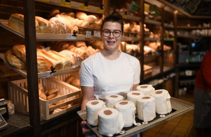 """<p class=""""Normal"""">Andrea Schulz, nhân viên học việc, bêkhay bánh mì hình cuộn giấy vệ sinh tại tiệm bánh Schuerener Backparadies ở Dortmund, Đức giữa lúc Covid-19 bùng phát.</p>  <p class=""""Normal"""">Tiệm bánh nơi Schulz làm việc bán loại bánh giấy vệ sinh, được phết kem bên ngoài và bọc kẹo mềm bên trong. Những """"cuộn giấy vệ sinh ngọt ngào""""trở nên đắt khách giữa cuộc khủng hoảng Covid-19.<br /> </p>"""