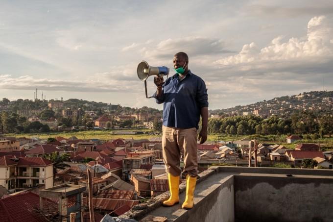 """<p class=""""Normal"""">Gonzaga Yiga, 49 tuổi, người đứng đầu khu dân cư, đứng trên tòa nhà cao nhất ở nơi mình sống thuộc Kampala, Uganda vào mỗi sáng và tối, cầm loa thông báo với mọi người về cách hạn chế lây nhiễm virus.</p>"""