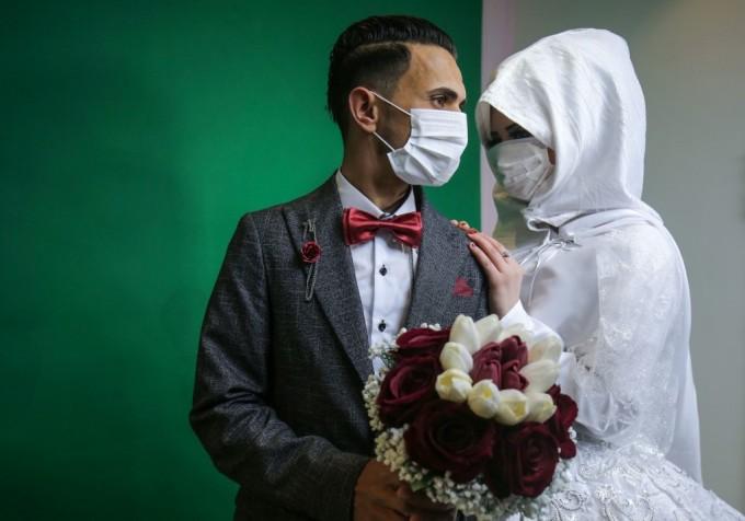 """<p class=""""Normal"""">Chú rể người Palestine Mohamed abu Daga và cô dâu đeo khẩu trang bảo vệ trong buổi chụp hình tại một studio, trước khi lễ cưới của họ được tổ chức ở Khan Yunis, phía nam dải Gaza.</p>  <p class=""""Normal"""">Chính quyền Gaza xác nhận hôm 22/3 hai ca nhiễm Covid-19 đầu tiên. Họ là người Palestine trở về từ Pakistan và đã được cách ly.<br /> </p>"""