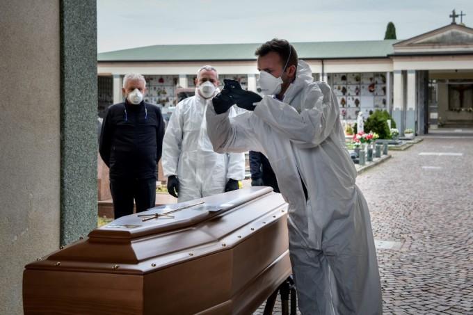 """<p class=""""Normal"""">Một người đàn ông chụp ảnh quan tài của người quá cố tại nghĩa trang Grassobbio, Bergamo, Italy. Người thân của người chết không thể tham dự lễ tang vì họ bị cách ly.</p>"""