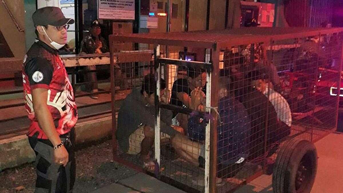 Nhóm 5 người vi phạm lệnh phong tỏa bị phạt ngồi trong chuồng chó. Ảnh: Fox News.