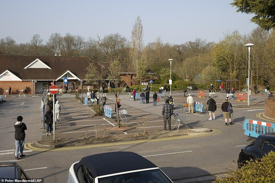 Khách hàng giữ khoảng cách khi xếp hàng bên ngoài siêu thị Tesco ở Leatherhead, Surrey, hôm 28/3. Ảnh: LNP.