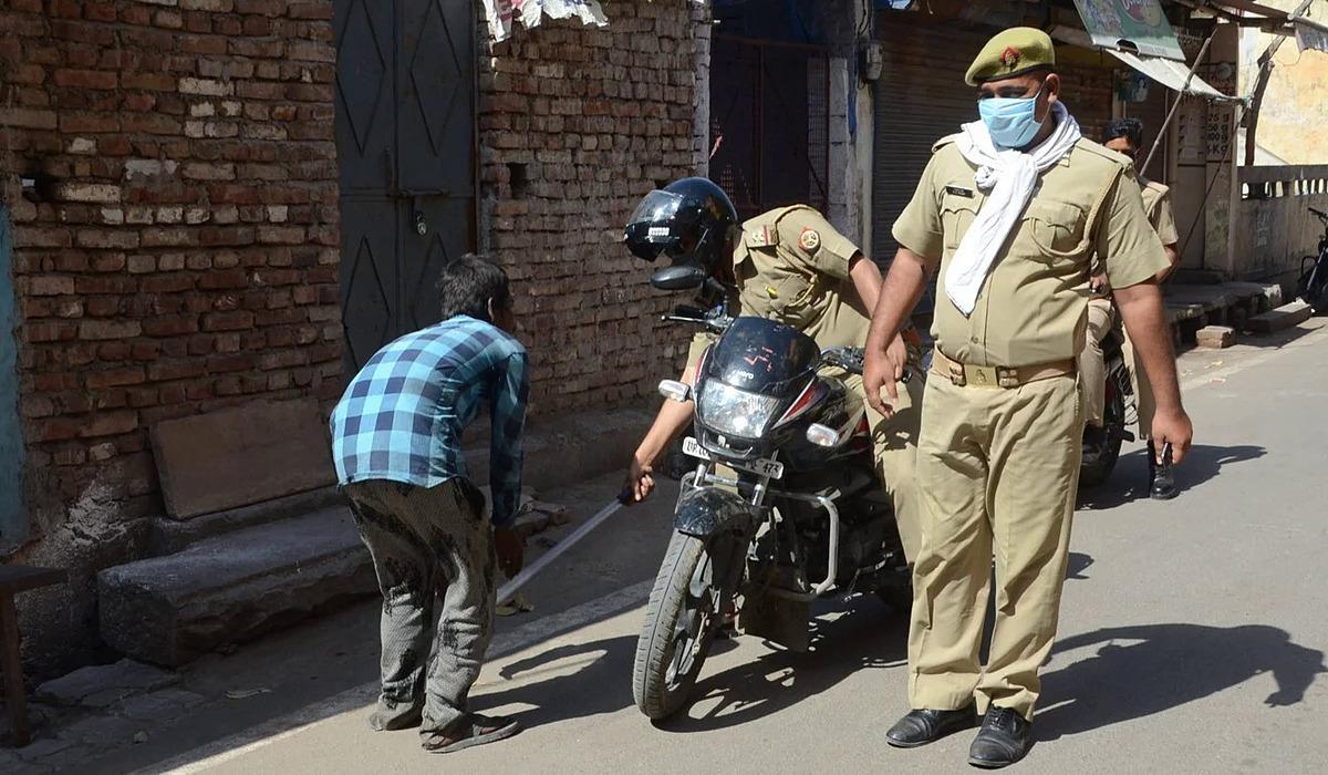 Một cảnh sát đánh đập người đàn ông bằng gậy vì không tuân thủ quy tắc trong thời gian phong tỏa. Ảnh: DPA.