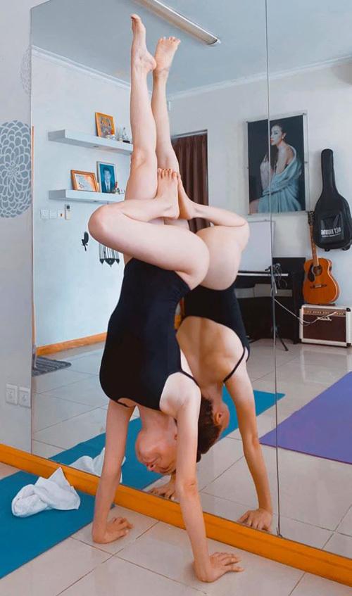 Trà Ngọc Hằng đã là mẹ một con nhưng vẫn có thân hình chuẩn mực. Yoga tại nhà cũng là bí quyết giữ sức khỏe của cô. Trồng cây chuối trong bộ bodysuit táo bạo, nữ ca sĩ khoe vòng ba quyến rũ.