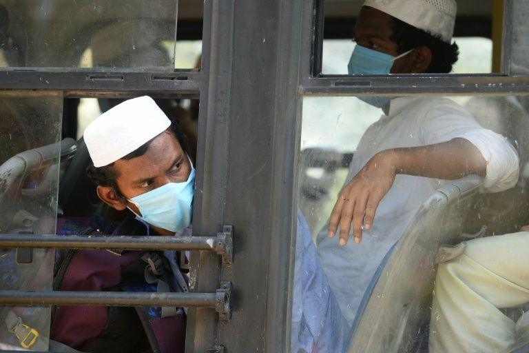 Những người đàn ông chờ đợi trên một chiếc xe buýt đưa họ đến một cơ sở cách ly sau khi họ tham dự buổi thánh lễ ở vùng Nizamuddin, New Delhi. Ảnh: AFP.
