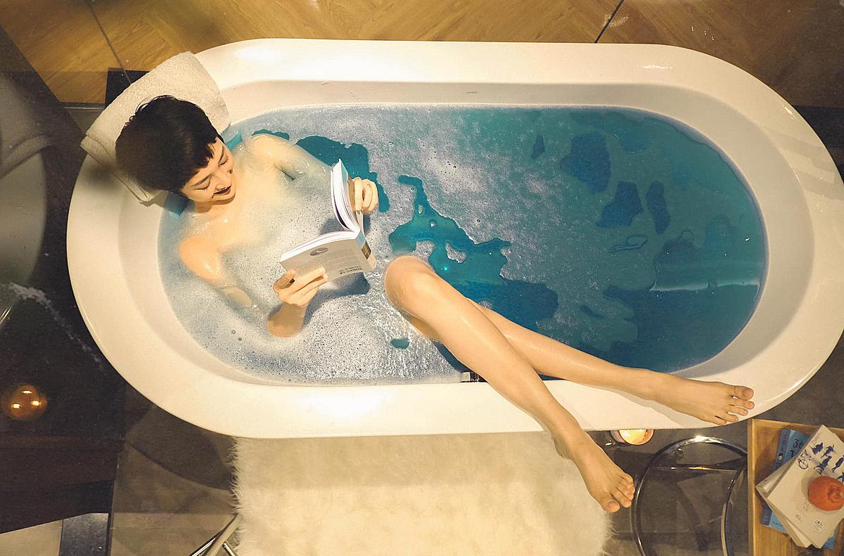 Bảo Anh nằm tắm bồn, đọc sách thư giãn.