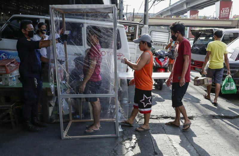 Nhân viên an ninh kiểm tra nhiệt độ cho những người vào khu chợ ở thủ đô Manila, Philippines hôm 4/4. Ảnh: AP.