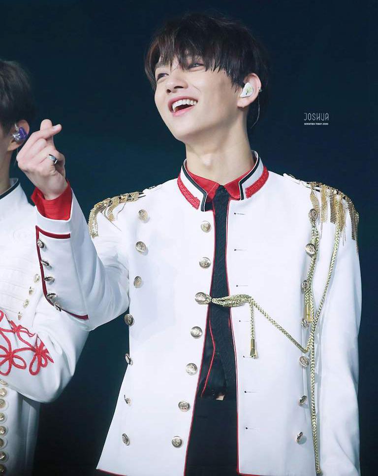 Nụ cười trong trẻo của Joshua (Seventeen) tại concert Ideal cut (2018) quả là cùng tông với bộ trang phục trắng được tạo điểm nhấn ở cầu vai và quai tết vàng.