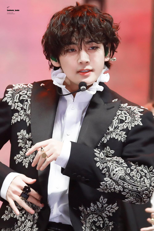 V (BTS) hóa hoàng tử khi mặc một chiếc áo lụa trắng, cổ bèo - loại áo phổ biến vào thế kỉ 18 - kết hợp với áo khoác ngoài được thêu họa tiết hoa lá nhỏ màu trắng, lấp lánh bắt mắt.