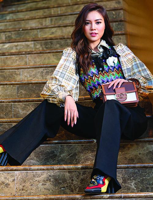 Cách mix áo gilet và sơ mi tay bồng cổ điển tiếp tục được Lan Ngọc áp dụng. Chất liệu kim sa đi cùng họa tiết caro là một sự kết hợp táo bạo của nhà mốt Louis Vuitton, thách thức cả những cô nàng vốn được khen mặc đẹp như Lan Ngọc.