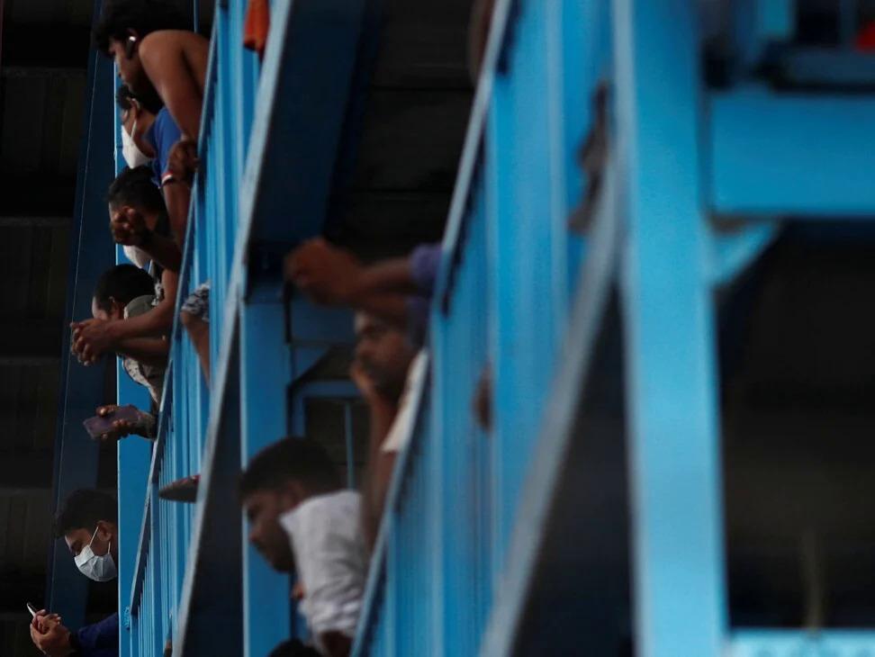 Công nhân Bangladesh và Ấn Độ đứng ở ban công tại Ký túc xá S11 vào ngày 6/4. Ảnh: Reuters.