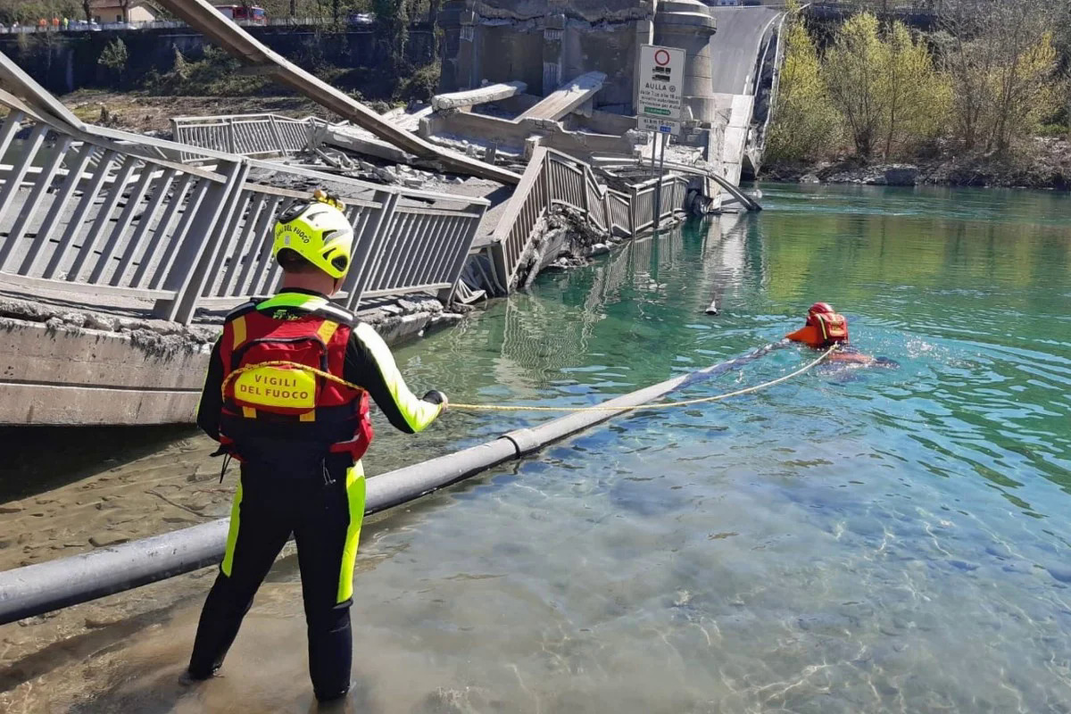 Lính cứu hộ tìm kiếm nơi cầu bị sập. Ảnh: EPA.