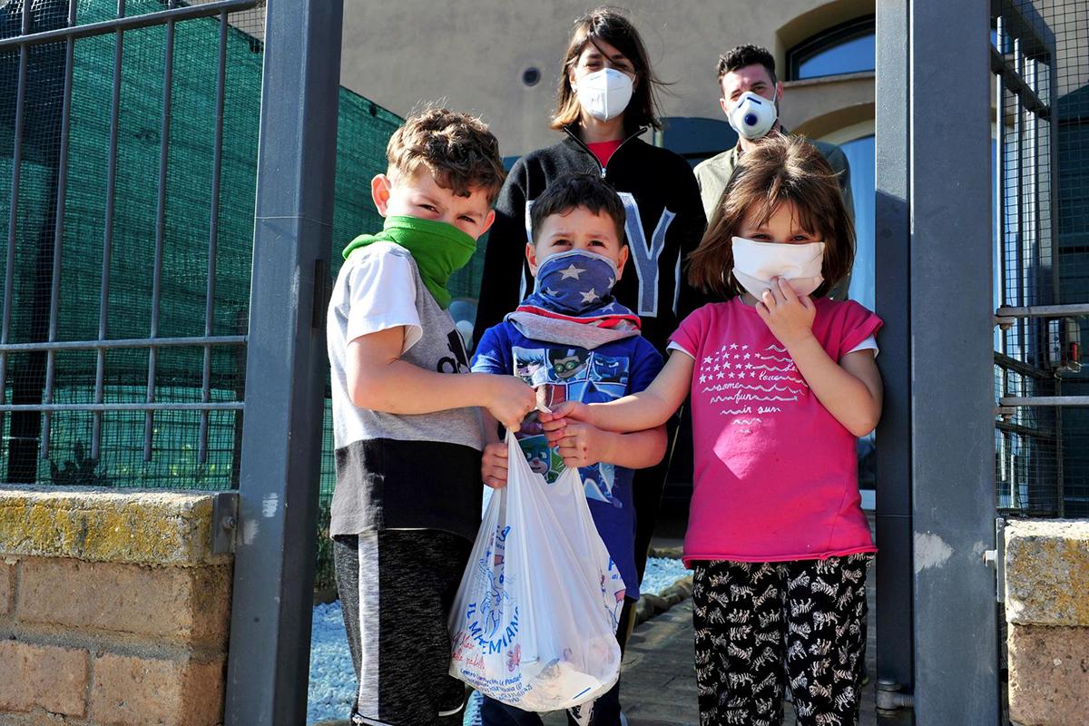 Một gia đình ở Italy nhận được cá từ các tình nguyện viên trong khi nước này vẫn phong tỏa vì dịch bệnh. Ảnh: Reuters.