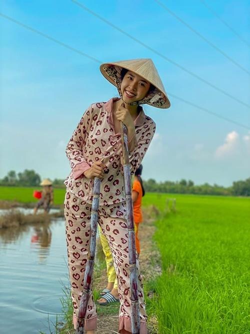 Á hậu Thúy An đội nón, mặc trang phục giản dị, ra đồng cấy lúa.