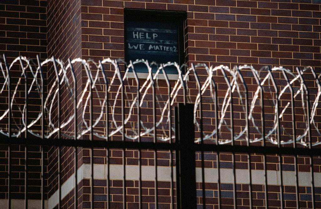 Các tù nhân treo biển cầu xin sự giúp đỡ trong một số cửa sổ ở nhà tù hạt Cook. Ảnh: Reuters.