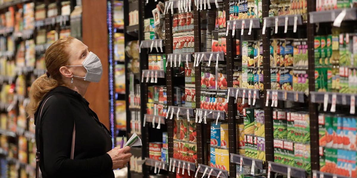 Một phụ nữ đeo khẩu trang khi mua sắm tại cửa hàng tạp hóa ở thành phố Salt Lake. Ảnh: AP.