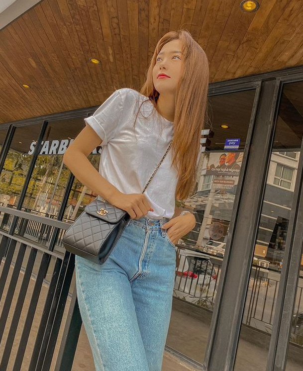 Ra ngoài trong những ngày dịch, Minh Hằng chọn cách lên đồ nhanh gọn nhất có thể. Cô diện áo phông trắng trơn màu với quần jeans, kết hợp thêm chiếc túi Chanel để làm điểm nhấn.