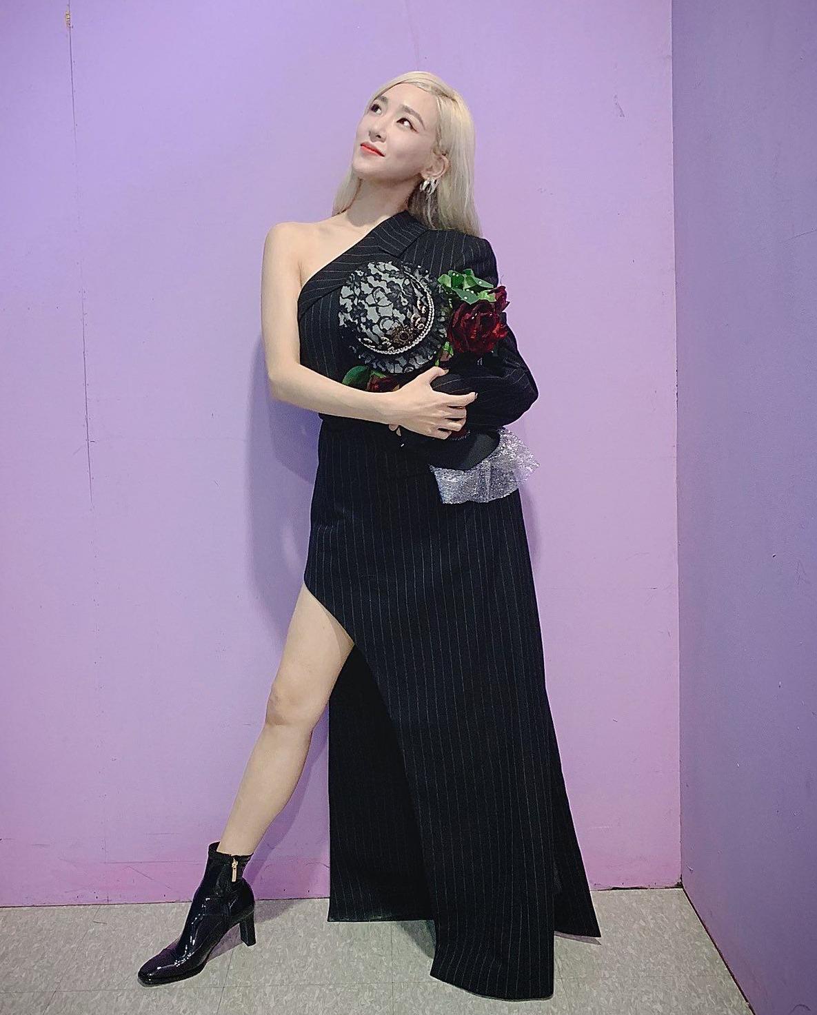 Mẫu váy thiết kế lệch vai đặc biệt lấy cảm hứng từ áo vest nam của nhà mốt Kimhekim được Tiffany kết hợp với boots đen cổ cao, tạo sự đồng điệu cho outfit của mình.