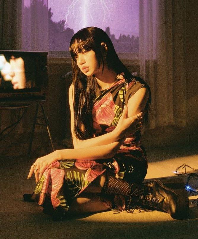 Lisa (Black Pink)  đem đến vẻ đẹp của nàng thơ mơ mộng khi diện váy hoa nhưng lại phá cách đầy cá tính với boot cao cổ hầm hố.
