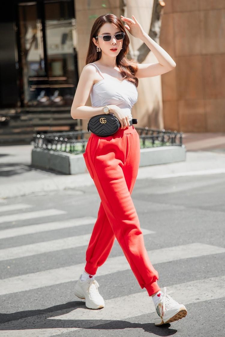 Áo hai dây ngắn khoe eo được Huỳnh Vy mix cùng quần thể thao cạp cao gam màu đỏ và sneaker độn đế. Chiếc belt-bag Gucci gam màu đen tạo diện mạo cá tính.