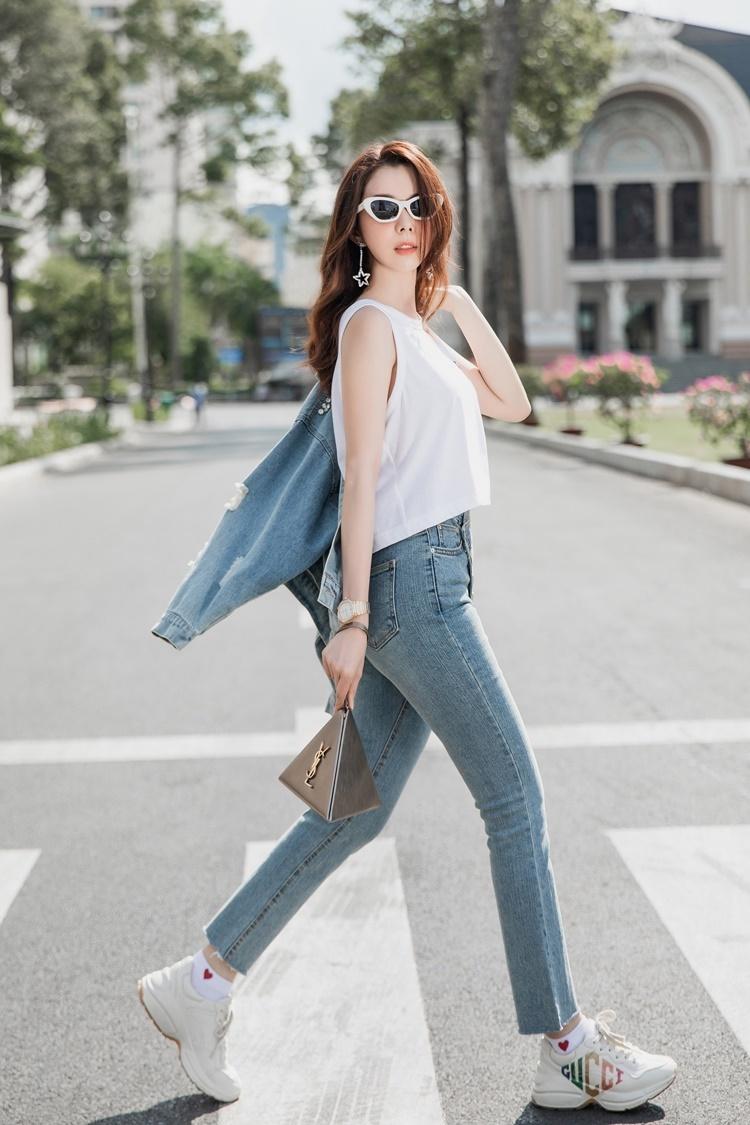 Huỳnh Vy mix chiếc túi có kiểu dáng lạ mắt của Yves Saint Laurent cùng trang phục denim và sneaker Gucci.