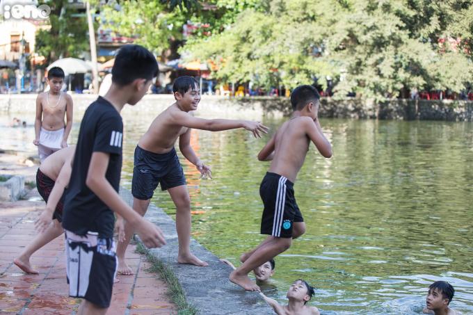 """<p class=""""Normal""""><span>Từ 16h, nhiều đứa trẻ đã đến để đi tắm và tập bơi. Nhiều emchạy lấy đà rồi lao xuống hồ hoặc được bạn bè đẩy xuống dưới sự hò hét cổ vũ.</span></p>"""