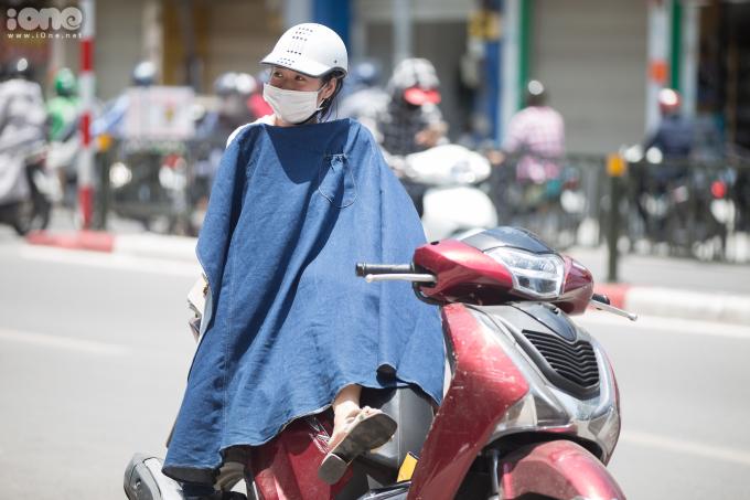 """<p class=""""Normal"""">Một cô gái trùm kín người che nắng trước một cửa hàng trên đường Tôn Đức Thắng.</p>  <p class=""""Normal"""">Chỉ số tia UV tại Hà Nội ở khoảng 8-10, ứng với mức ảnh hưởng nguy cơ gây hại từ cao đến rất cao đối với cơ thể con người khi tiếp xúc trực tiếp với ánh nắng.</p>"""