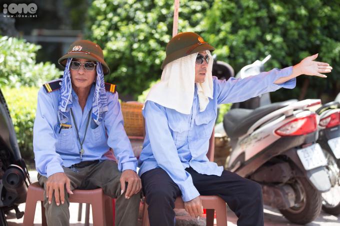 """<p class=""""Normal"""">Anh Nguyễn Đức Chung (bên phải) đội mũ cối vàtrùm kín đầu bằng khăn mát để thấm mồ hôi và tránh ánh nắng khi làm việc ngoài trời.</p>"""