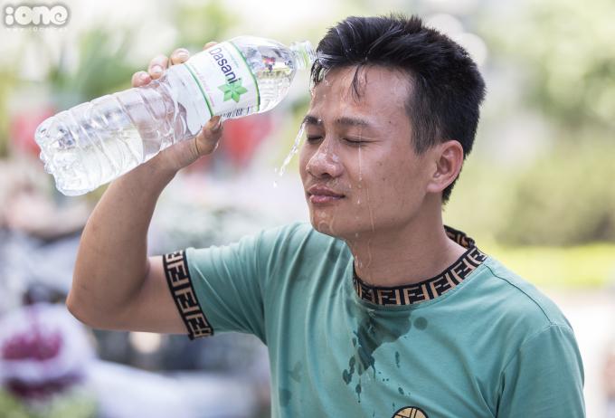 <p>Trên đường Lê Văn Lương, người đàn ông này đang dội nước lên mặt để làm dịu mát cơ thể.</p>