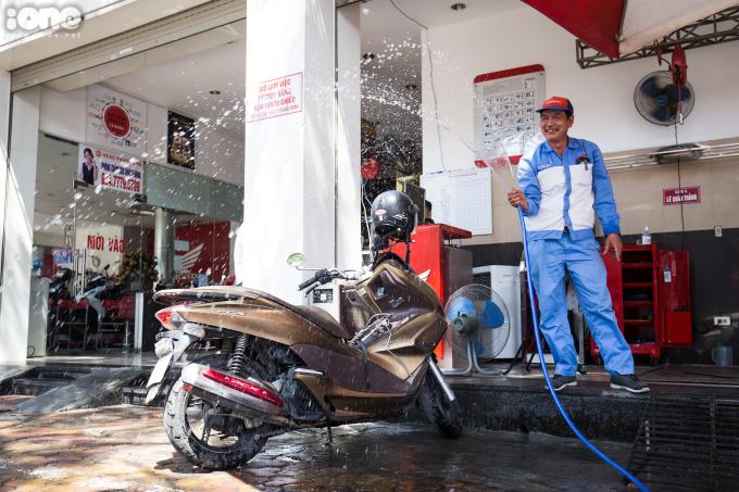 <p>Một người đàn ông phun nước lên vỉa hè trước cửa hàng với hy vọng nền nhiệt sẽ giảm đôi chút.</p>