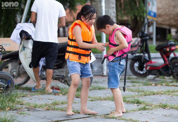"""<p class=""""Normal""""><span>Ở đây, các em nhỏ được bố mẹ trang bị áo phao đầy đủ. </span>Em Nguyễn Khánh Chi -lớp 2trường tiểu học Sài Sơn (áo phao cam) nói: """"Hai hôm nay, hai chị em con đều ra đây tắm và rấtthích"""".</p>"""