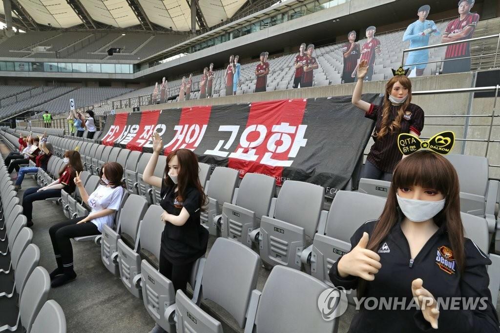 Các hình nộm búp bê nữ cũng được sắp xếp ngồi giãn cách, đeo khẩu trang trên khán đàiSVĐ Seoul World Cup.