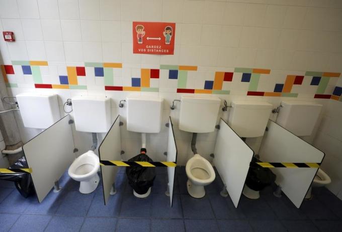 """<p class=""""Normal""""><span>Tấm biển ghi chú""""Hãy giữ khoảng cách"""" được gắn phía trên tường của nhà vệ sinh tại mộttrường tiểu học ở Nice, Pháp.</span></p>"""