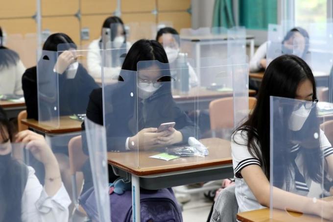 """<p class=""""Normal""""><span>Học sinh trung học tại Daejeon, Hàn Quốc đeo khẩu trang trong lớp hôm 20/5. Trên bàn học,</span><span>tấm chắn nhựa trong suốtđược lắp đặt nhằm ngăn chặnCovid-19 lây lan.</span></p>"""