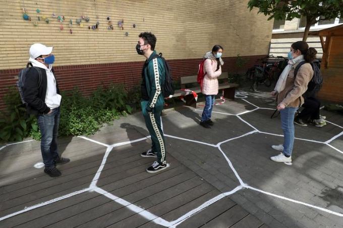 """<p class=""""Normal""""><span>Học sinh nói chuyện với nhau trong khi vẫn đeo khẩu trang tại sântrường trung học ởBrussels, Bỉ, ngày 15/5.</span></p>"""