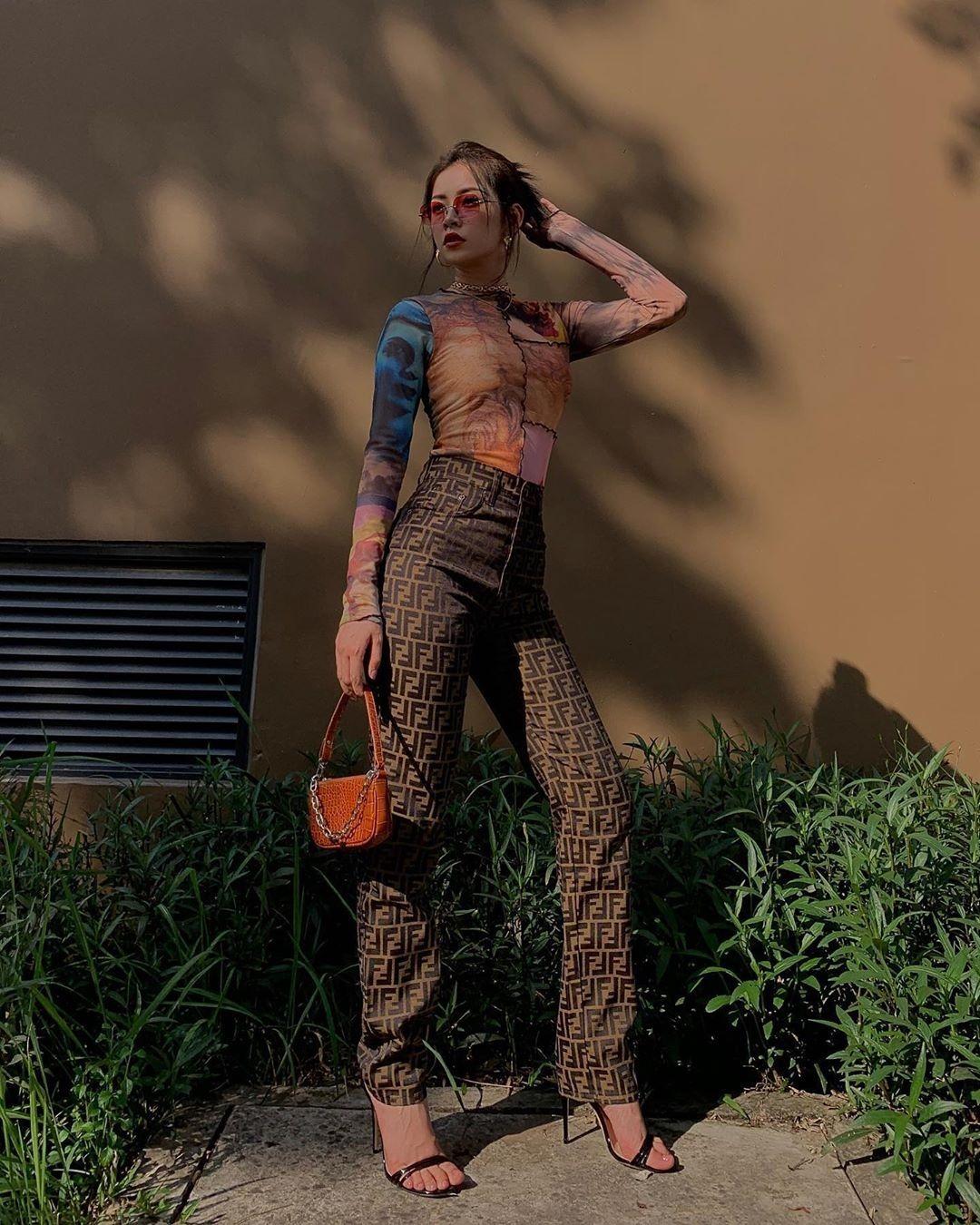 Set đồ của Chi Pu mang đậm cảm hứng năm 90 với áo tay dài bó sát đi kèm quần ống loe của Fendi. Nữ ca sĩ cũng rất tinh tế khi chọn phụ kiện retro để mix-match.