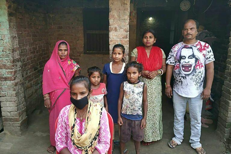 Jyoti Kumari Paswan (người đeo mặt nạ), đứng cùng gia đình bên ngoài nhà của họ ở bang Bihar phía đông bắc. Ảnh: AFP / STR.