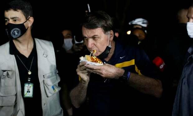 Tổng thống Bolsonaro ăn hot dog khi xuống phố.